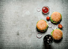Three burgers with a soda on stone table. royalty free stock image