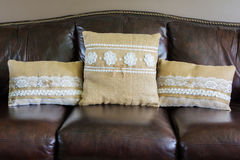 Three Burlap Pillows with White Lace on a Leather Couch Stock Images