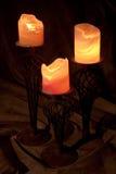 Three burning candles. Closeup of three decorative burning candles on ornate holders, dark background royalty free stock photos