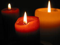 Three burning candles. Three candles burning in the dark, focus on the front candle Stock Images