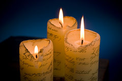 Three burning candles. Close up of three burning candles in the dark stock image