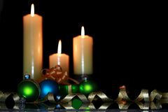 Three burning candles with Christmas ornaments Stock Photography