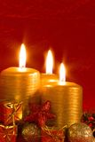 Three burning candles in a Christmas setting Royalty Free Stock Photography