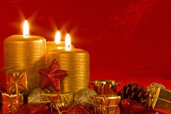 Three burning candles in a Christmas setting. With seasonal decorations Royalty Free Stock Photos