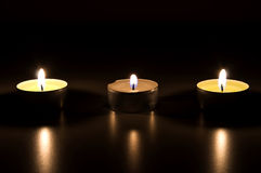 Three burning candles in the dark Royalty Free Stock Photo