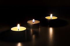 Three burning candles in the dark Royalty Free Stock Image