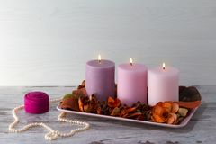 Three burning candles on stand with dry decorative flowers and bark. Pearl necklace and box for ring on light gray royalty free stock photos