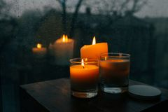 Three burning candles on table, cozy rainy day an home. Hygge interior decor royalty free stock photo