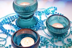 Three burning candles in turquoise candlesticks with a Christmas garland on a white background stock image