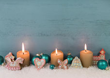Three burning candles on wooden blue shabby wooden background. Royalty Free Stock Images