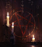 Three burning candles and wooden planks with pentagram. Three burning candles against the background of wooden planks with bloody pentagram. Halloween concept royalty free stock photo
