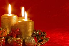 Three burning Christmas candles. Three burning candles in a Christmas setting with seasonal decorations Royalty Free Stock Photos