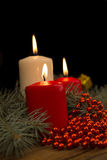 Three burning Christmas candles on the background of fir-tree br Royalty Free Stock Photo