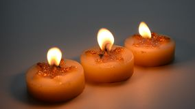 Three burning decorative candles with star pattern stock video footage