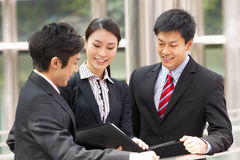 Three Business Colleagues Discussing Document Stock Photo
