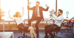 Fun moments in sunny modern office. Three Business Colleagues Handing Up In Sunny Modern Office To Express Finish Of Successful Project. Business Concept stock image