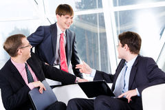 Three business men. Are discussing a terms of transaction Royalty Free Stock Image