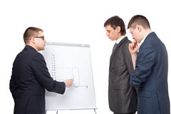 Three business men and flipchart Stock Photos