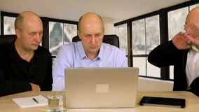 Three business men sitting at table front laptop and discussing business project stock video footage