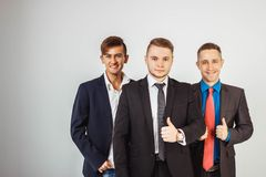Three business men in suits standing like a team Stock Images