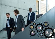 Three business men walking down stairs and black gear graphics Stock Image