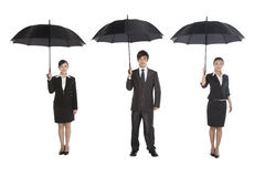 Three business people holding umbrella Royalty Free Stock Image