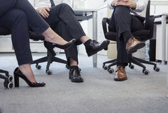 Three business people with legs crossed sitting on chairs, low section Stock Photo