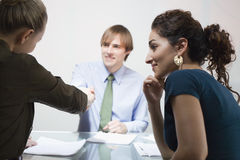 Three Business people in Meeting. Three businesspeople in meeting. A male and female are shaking hands. Horizontally framed shot Stock Photos