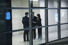 Three business people meeting, seen through glass wall Stock Image