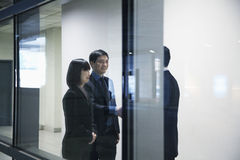 Three business people meeting and shaking hands, seen through glass wall Royalty Free Stock Photography