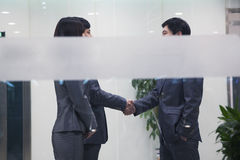 Three business people meeting and shaking hands, seen through glass wall Stock Images