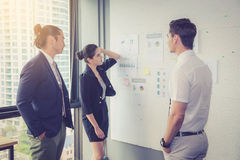 Three business people in modern office looking report and analyzing. Royalty Free Stock Photo