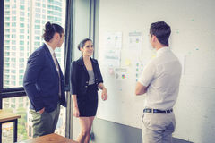 Three business people in modern office looking report and analyzing. Royalty Free Stock Photography