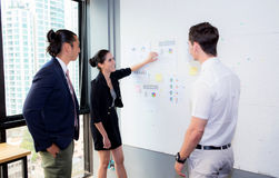 three business people in modern office looking report and analyzing. Stock Images