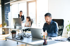 Three business people in the office working together. Stock Images