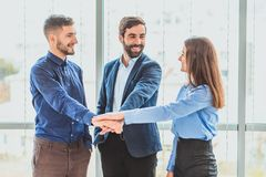 Three business people placing a contract put a hand on hand. royalty free stock photos