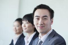 Three Business People in a row smiling Royalty Free Stock Images