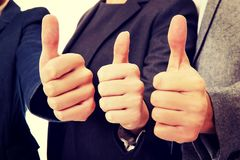 Three business people showing thumbs up stock photo