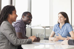Three business people sitting at a conference table and discussing during a business meeting royalty free stock image