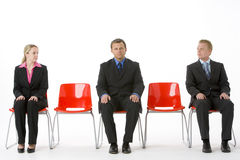 Three Business People Sitting On Red Plastic Seats Stock Photo