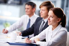 Business seminar. Three business people sitting at seminar, the focus is on woman royalty free stock image