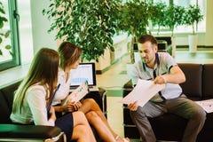 Three business people sitting on sofa holding folders and having conversation Stock Photos