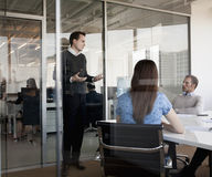 Three business people sitting, standing, and discussing during a business meeting Stock Photos