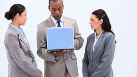 Three business people using a laptop Stock Image