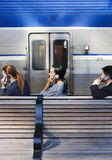 Three business people using mobile phones on railway platform beside stationary passenger train, profile Stock Images