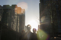 Three business people walking down a city street with sunlight at their back, lens flare Stock Photo
