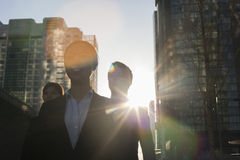 Three business people walking down a city street with sunlight at their back, lens flare Royalty Free Stock Photography