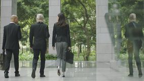 Three business people walking out of modern office building. Multinational corporate businessmen and businesswoman leaving walking out of modern office building Royalty Free Stock Photography