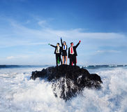 Three Business People Wearing Superhero Costumes. Posing on a rock with gushing waves Royalty Free Stock Photography