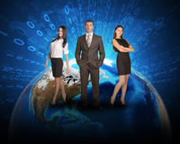 Three business person standing on Earth surface. Background is world map with ray of figures. Elements of this image furnished by NASA Stock Images